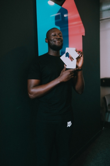 Stormzy with his Official Number 1 Single Award for Vossi Bop (Credit: Kaylum Dennis)